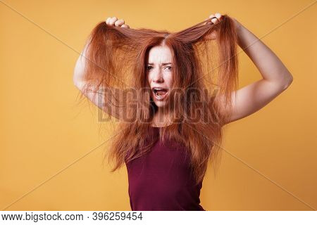 Frustrated Young Woman Pulling And Tearing Her Long Red Hair On A Bad Hair Day