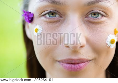Young Fresh Womans Face With Wild Flowers And Daisy. Woman Eyes With Natural Make-up. Natural Cosmet