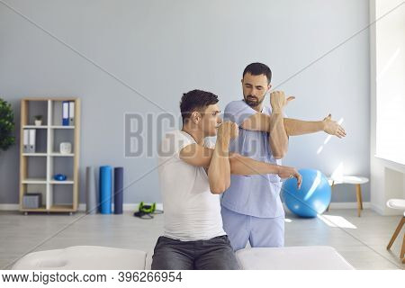 Physiotherapist Teaching Patient To Do Cross-body Stretch To Ease Pain And Cure Shoulder Stiffness