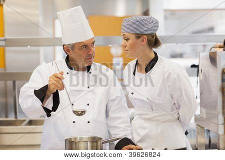 Student and teacher discussing the soup in kitchen