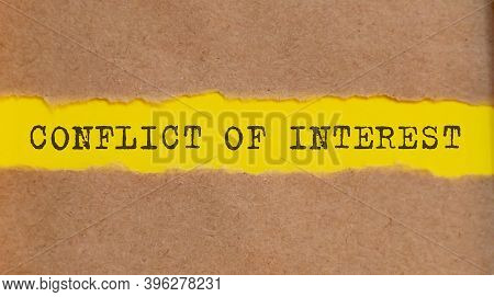 Conflict Of Interest Written Under Torn Paper On The Yellow Background