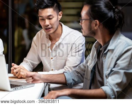 Portrait of Asian businessman working late having meeting with business team to brainstorm idea at office meeting room. Work hard deadline and overtime working and new business start up concept.