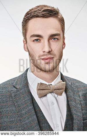 Portrait of a good looking handsome man wearing elegant classic suit and a bow-tie on a white background. Men's beauty, fashion.