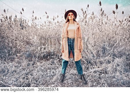 Winter fashion. Full length portrait of a beautiful young woman in trendy  clothes posing next to the reeds on the background of the winter landscape.
