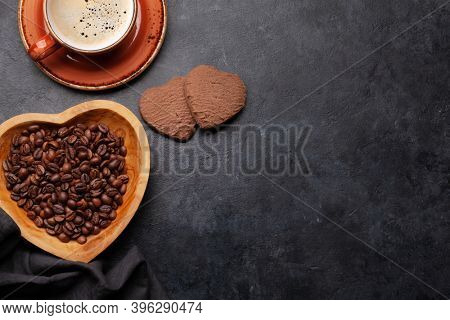 Roasted coffee beans in heart shaped bowl, cup and gingerbread cookies on stone table. Love coffee concept. Top view flat lay with copy space