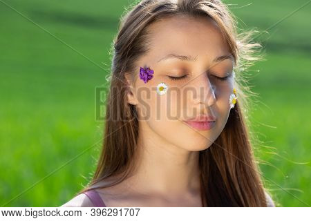Gorgeous Model Long-haired Pretty Girl Posing Eyes Closed With Wild Flowers On Her Face On Blurred G