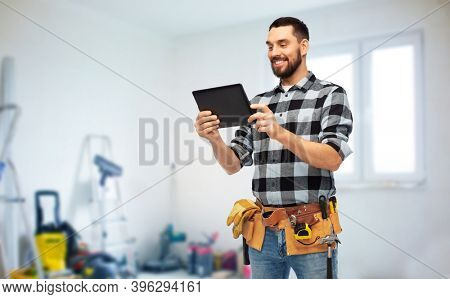 technology, construction and repair concept - happy smiling worker or builder with tablet pc computer and tools over room with building equipment background