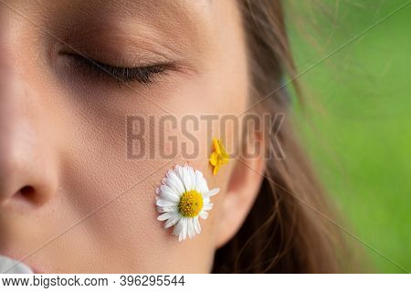 Macro Shot Of Daisy And Wild Flower On Womans Beautiful Face Eyes Closed. Womens Skincare. Beautiful