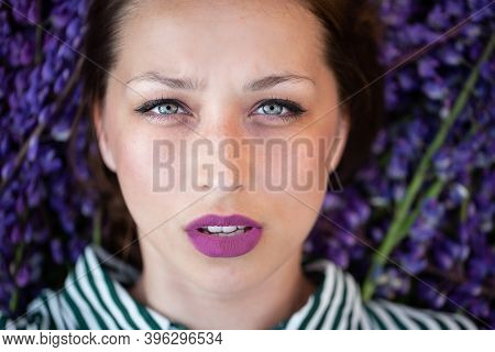 Beautiful Young Girl Lies In Violet Lupine Flowers Looking At Camera. Glamor. Makeup - Arrows, Purpl