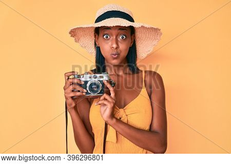 Young african american woman wearing summer hat holding vintage camera puffing cheeks with funny face. mouth inflated with air, catching air.