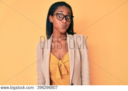 Young african american woman wearing business clothes puffing cheeks with funny face. mouth inflated with air, crazy expression.