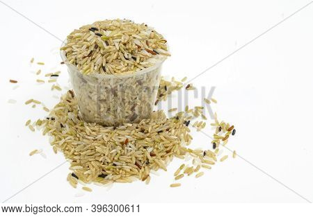 Isolated Raw Mix Brown Rice In Plastic Measuring Rice Cup On White Background. Close Up Organic Raw