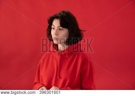 Tired Brunette Girl In Red Hoodie Posing On Red Studio Backdrop Copy Space. Pain, Fatigue, Tension C