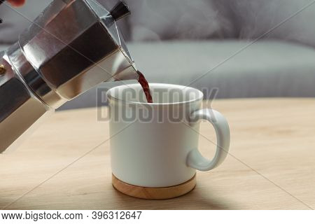 Pour The Coffee Into Ceramic Cup On Wooden Table