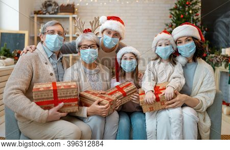 Merry Christmas and Happy Holidays! Grandparents, dad, mum and children exchanging gifts. Parents and daughters wearing face masks near tree indoors. Loving family with presents in room.