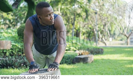 African American Muscular Young Man Exercising In Green Forest Park.african Sportsman Warm-up In Pus