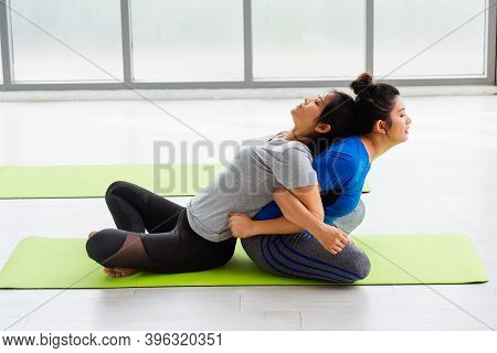 Two Asian Women Sporty Attractive People Practicing Yoga Lesson Together, Working Out At The Fitness