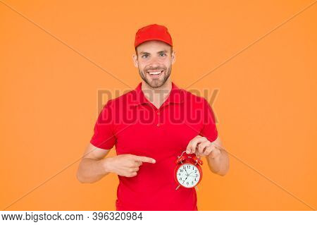 Always In Time. Happy Man With Alarm Clock On Yellow Background. Delivering Your Purchase. Courier S