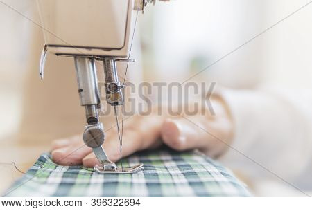 Closeup View Of The Sewing Process - Female Hands Sewing Fabric On Professional Machine - Elderly Wo