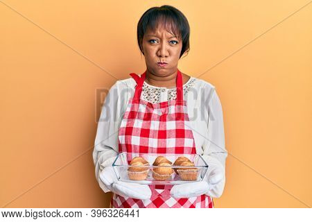 Middle age african american woman wearing baker apron holding muffins puffing cheeks with funny face. mouth inflated with air, catching air.