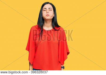 Beautiful young woman wearing casual clothes puffing cheeks with funny face. mouth inflated with air, crazy expression.