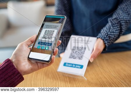 Close up of woman hand holding smartphone and scanning qr code for digital payment. Customer paying money online using mobile phone after shopping. Girl using cellphone scanner to scan qr code.
