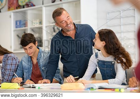 Happy mature professor helping student girl with her doubts while studying in class. Smiling teacher in high school helping student. Group of young college classmates in classroom with helpful teacher