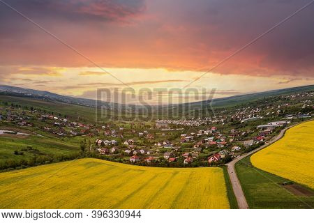 Aerial View Of Ground Road With Moving Cars In Green Fields With Blooming Rapeseed Plants, Suburb Ho