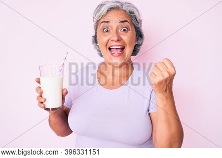 Senior hispanic woman holding glass of milk screaming proud, celebrating victory and success very excited with raised arms