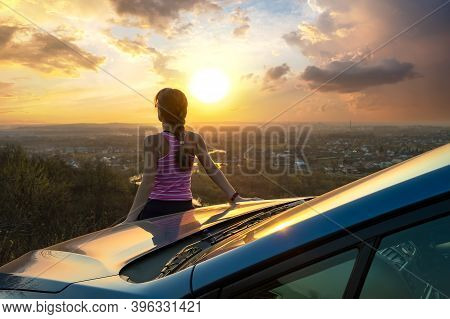Young Woman Driver Standing Near Her Car Enjoying Warm Sunset View. Girl Traveler Leaning On Vehicle