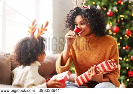 Happy  Family: Delighted Mother   With Son Playing As Santa's Reindeer With A Red Nose While Having