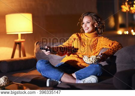 Young  Cheerful Woman Eating Popcorn And Watches  Movie On  Cable Tv While Switching Channels With T