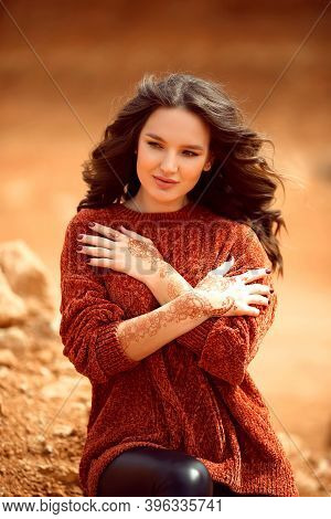 Henna Mehndi. Mehendi On Hands. Outdoor Portrait Of Attractive Woman In Sweater With Curly Hair.