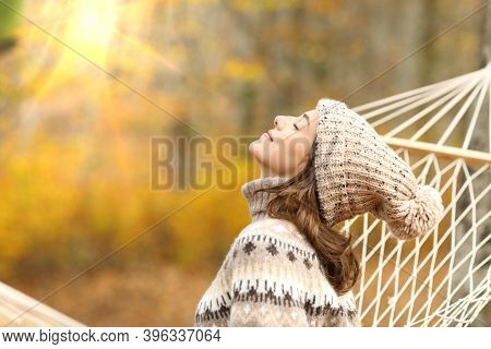 Side View Portrait Of A Relaxed Woman Breathing Fresh Air Sitting On A Rope Hammock In Autumn In A F