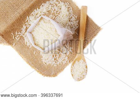 Isolated Rice On Wooden Spoon. Top View Raw And Uncooked Rice In Wooden Spoon On Hemp Sackcloth Over