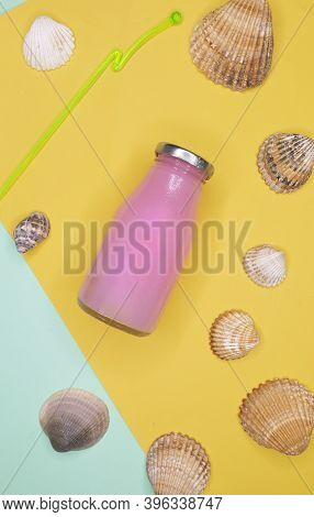 Flat Lay Glass Jug With A Strawberry Smoothie Surrounded By Seashells