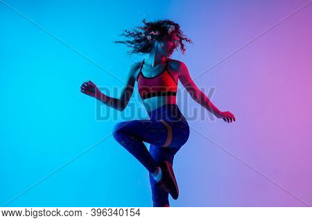 Sport Dancing. Beautiful Woman In Bright Sportwear Isolated On Gradient Pink-blue Background In Neon