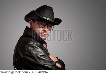 Unshaven Young Man With Glasses, A Hat And A Black Cloak. Cowboy Portrait Of A Man, Western Culture,