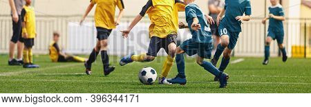 Horizontal Image Of Football Players Kicking Match. Boys In Soccer Duel. Kids In Two Football Teams