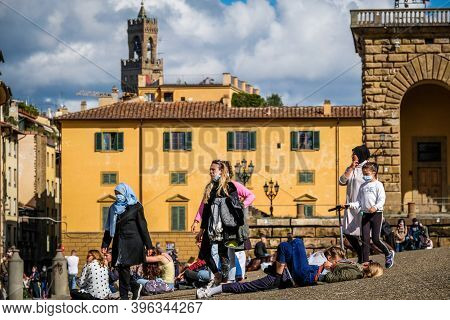 2020 October 17, Florence Italy: Tourists Seated Near The Palazzo Pitti Or The Pitti Palace, Is A Va