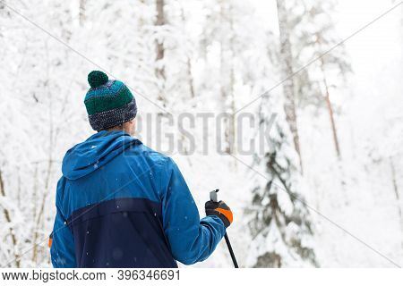 Skier In Windbreaker And Hat With Pompom With Ski Poles In His Hands With His Back Against The Backg