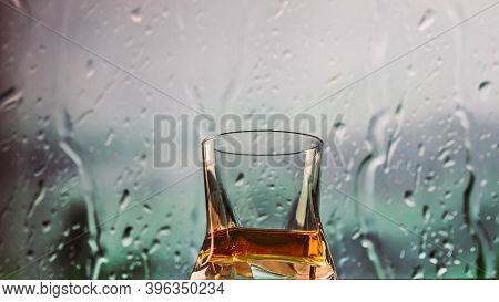 Whiskey In A Glass Close-up, Rain Background, Alcoholic Drink By The Window On The Bar.