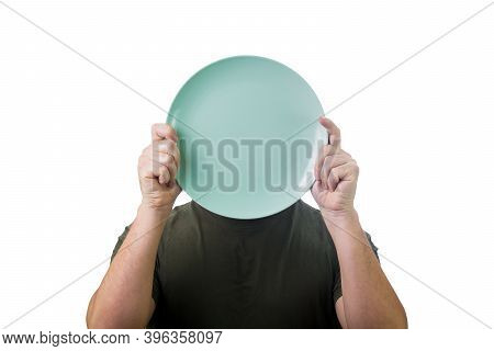 Anonymous Man Hiding His Identity, Covering Face Using An Empty Dish Plate. Global Crisis And Hunger