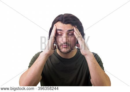 Portrait Of Exhausted Young Man Keeps Hands To Temples, Eyes Closed, Feels Headache Isolated On Whit