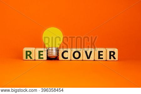 Recover Concept. Wooden Cubes With Word 'recover'. Yellow Light Bulb. Beautiful Orange Background. B