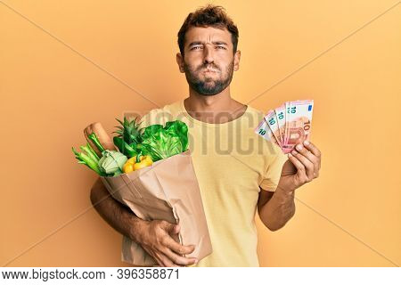 Handsome man with beard holding groceries and 10 euros banknotes puffing cheeks with funny face. mouth inflated with air, catching air.
