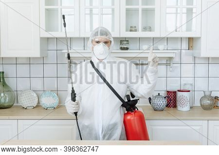 A Man In The Kitchen In A Protective Suit With A Disinfectant Spray To Disinfect Household Items And