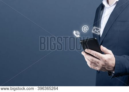 Contact Us. Businessman Holding Cell Mobile Phone With With Mail, Phone, Email Icon. Cutomer Support