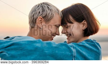Close Up Of Young Loving Lesbian Couple Hugging And Looking At Each Other Before Kiss While Admiring