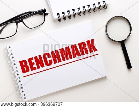 The Word Benchmark Is Written In A White Notebook On A Light Background Near The Notebook, Black-fra